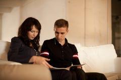Симпатичные пары читая книгу совместно Стоковые Изображения