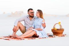 Симпатичные привлекательные пары сидя совместно на пляже с белым песком, счастливой паре сидя на одеяле, счастливых парах наслажд Стоковые Фото
