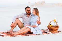 Симпатичные привлекательные пары сидя совместно на пляже с белым песком, счастливой паре сидя на одеяле, счастливых парах наслажд Стоковая Фотография