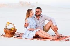 Симпатичные привлекательные пары сидя совместно на пляже с белым песком, счастливой паре сидя на одеяле, счастливых парах наслажд Стоковая Фотография RF