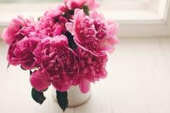 Симпатичные розовые пионы на деревенском белом деревянном окне в li утра Стоковые Изображения