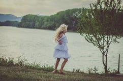 Симпатичные танцы ребенка на озере стоковая фотография