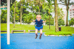 Симпатичный белокурый мальчик на качании в парке Прелестный мальчик имея потеху на спортивной площадке стоковая фотография rf