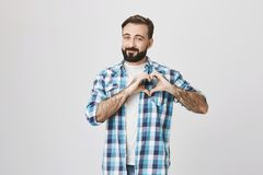 Симпатичный бородатый парень, усмехаясь задушевно делающ жест сердца около комода и положение около серой предпосылки Выставки су стоковые фотографии rf