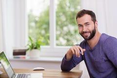 Симпатичный бородатый человек в домашнем офисе Стоковые Изображения RF