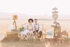 Симпатичный горизонтальный портрет новобрачных одетых годом сбора винограда сидя с собаками на софе окруженной с Стоковое Изображение