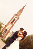 Симпатичный жених и невеста перед церковью Стоковые Изображения