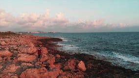 Симпатичный женский фотограф принимая фото огромных волн моря и скалистого побережья на красивый розовый заход солнца с городом P акции видеоматериалы