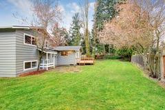 Симпатичный задний двор с палубой и травой Стоковые Изображения