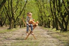 Симпатичный мальчик сидя на стуле с плюшевым медвежонком на весеннем времени Карее дерево Стоковая Фотография
