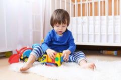 Симпатичный мальчик в голубой рубашке играет автомобили дома Стоковое фото RF