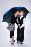 Симпатичный мальчик и девушка стоя под зонтиком Стоковые Изображения RF