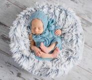 Симпатичный младенец в шляпе и комбинезоне спать на круглой кровати стоковые фото
