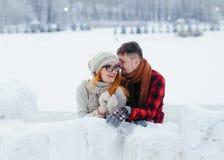 Симпатичный портрет красивых счастливых любящих пар обнимая пока полагающся на стене снега в деревне зимы стоковые изображения rf