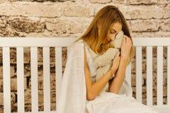 Симпатичный портрет портрета девочка-подростка обнимая плюшевый медвежонка пока сидящ на белом стенде Стоковые Фото