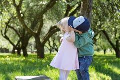 Симпатичный поцелуй детей в парке человек влюбленности поцелуя принципиальной схемы к женщине стоковые изображения