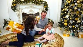 Симпатичный праздник семьи внутри подарки обменом заманчивости в большой светлой комнате на предпосылке праздничных деревьев и сток-видео