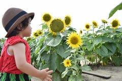 Симпатичный ребенок вокруг летних каникулов цветка солнца Стоковые Изображения RF
