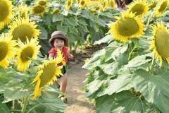 Симпатичный ребенок вокруг летних каникулов цветка солнца Стоковая Фотография