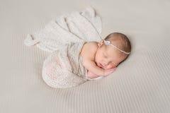 Симпатичный спать младенец обернутый в серой теплой пеленке стоковые фото