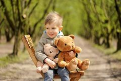 Симпатичный, усмехаясь мальчик сидя на стуле с плюшевым медвежонком на весеннем времени Карее дерево Стоковое Изображение RF