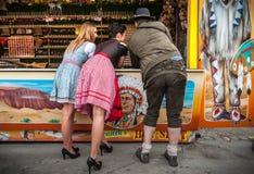 2 симпатичных девушки, один человек играя игры стрельбы и имея потеху на немецкий носить Oktoberfest ярмарки традиционный Стоковая Фотография RF