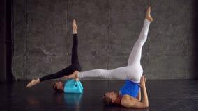 2 симпатичных женщины йоги делая йогу совместно в студии с большими окнами Женщины делая занятия йогой Пара делает йогу видеоматериал