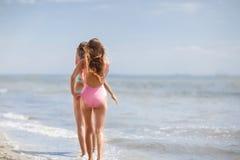 2 симпатичных маленькой девочки в красочных купальниках на предпосылке моря Дамы идя вдоль пляжа скопируйте космос Стоковое Фото