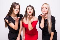 3 симпатичных молодой женщины в платьях ночи посылают поцелуи над белизной Стоковая Фотография