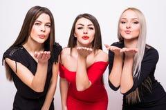 3 симпатичных молодой женщины в платьях ночи посылают поцелуи над белизной Стоковое фото RF