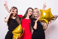 3 симпатичных молодой женщины имеют потеху и держать воздушные шары сформированные звездой над белизной Стоковое Фото