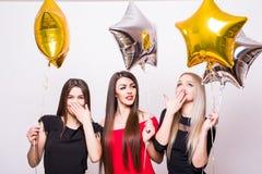 3 симпатичных молодой женщины имеют потеху и держать воздушные шары сформированные звездой над белизной Стоковое Изображение RF