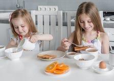 2 симпатичных сестры есть здоровый завтрак Стоковые Фотографии RF