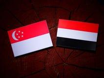 Сингапурский флаг с йеменским флагом на пне дерева Стоковое Фото