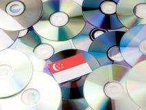 Сингапурский флаг na górze кучи КОМПАКТНОГО ДИСКА и DVD изолированной на белизне Стоковые Фото