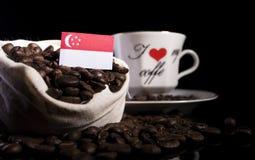 Сингапурский флаг в сумке с кофейными зернами на черноте Стоковая Фотография