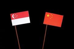 Сингапурский флаг с китайцем сигнализирует изолированный на черноте Стоковая Фотография