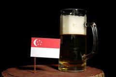 Сингапурский флаг с кружкой пива на черноте Стоковые Фотографии RF