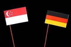 Сингапурский флаг с немецким флагом на черноте Стоковое Фото