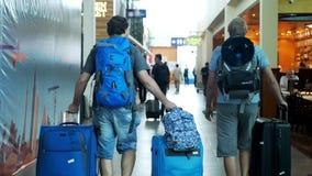 Сингапур, 13-ое июля 2018 Путешествуя человек 2 с рюкзаками идя в аэропорт вытягивает чемоданы стоковое изображение rf