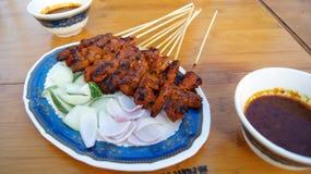 СИНГАПУР - 3-ье апреля 2015: Очень вкусные вкусные протыкальники цыпленка варят над горячими углями в еде улицы ` s Satay Сингапу стоковые изображения rf