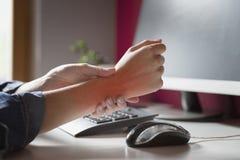 Синдром офиса - молодое женское страдание от боли руки пока мы стоковое фото