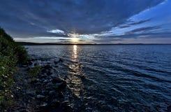 Синее небо над озером, оранжевое солнце вечера стоковые фотографии rf