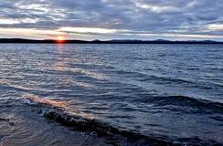 Синее небо над озером, оранжевое солнце вечера стоковые изображения rf