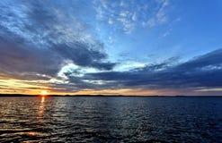 Синее небо над озером, оранжевое солнце вечера стоковое фото rf