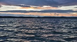 Синее небо над озером, оранжевое солнце вечера стоковое изображение