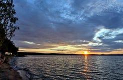 Синее небо над озером, оранжевое солнце вечера стоковая фотография rf