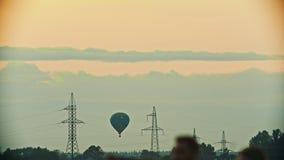 Сине-и-желтое летание воздушного шара над полем - башнями связи, башнями антенны - вечер акции видеоматериалы