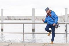 Синий пиджак задумчивого взрослого человека нося и smartphone использования стоковые фотографии rf