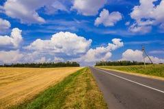 синь заволакивает белизна неба дороги затемненного поле стоковая фотография